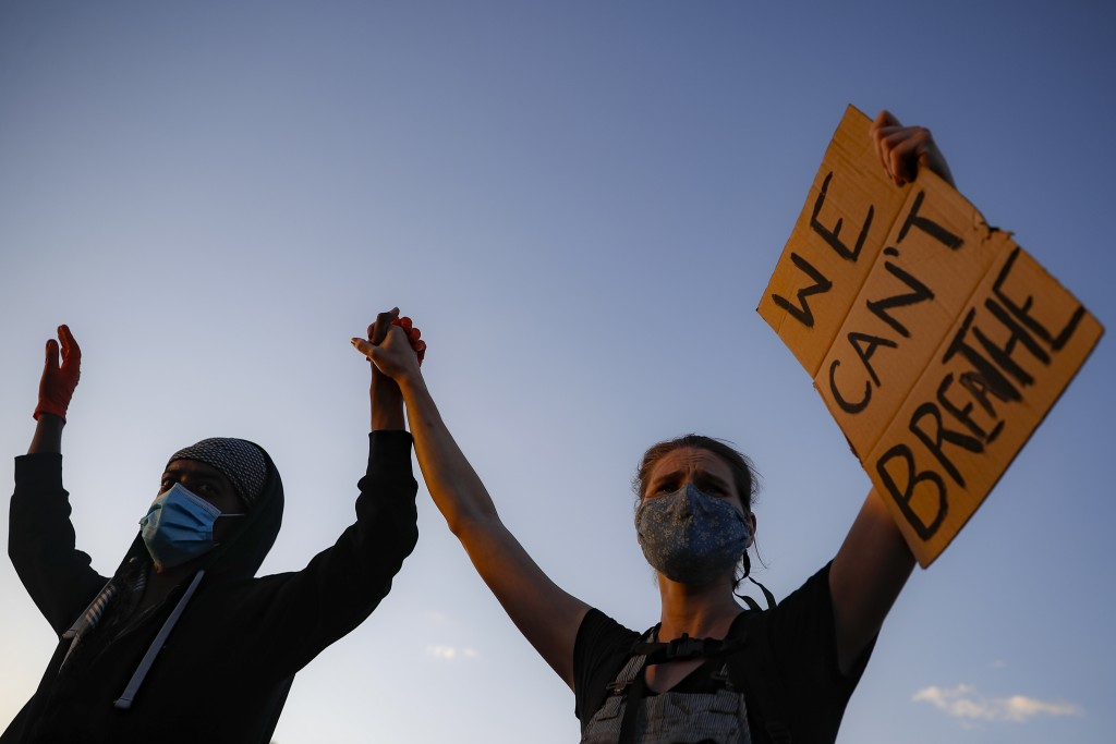 "Protestors demonstrate on University Avenue while holding a ""WE CAN'T BREATHE"" sign and wearing protective masks, Thursday, May 28, 2020, in St. Paul,..."
