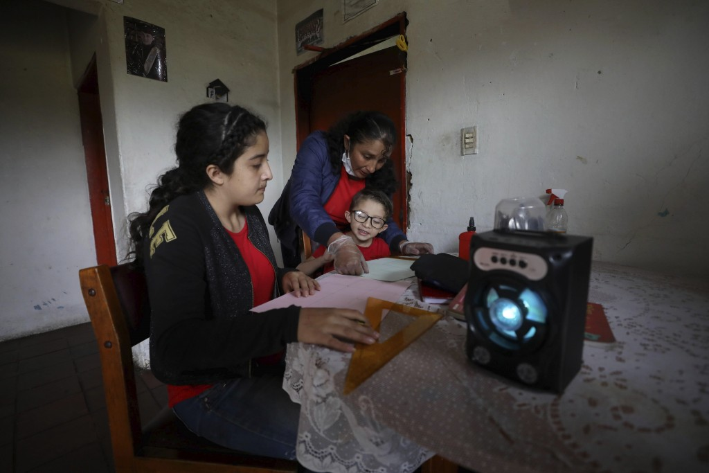 Fanny Mendez, right, mother of 14-year-old Marlene Beltran, left, and Felipe Beltrán, 5, helps her children at home to make a cube out of paper as the...