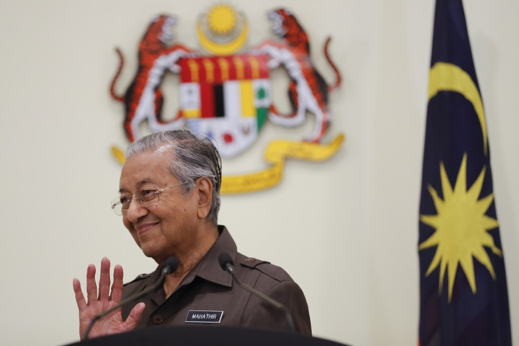 FILE - In this April 15, 2019, file photo, Malaysian Prime Minister Mahathir Mohamad waves good bye to media after a press conference in Putrajaya, Ma...
