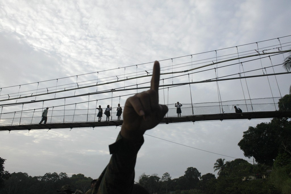 FILE - In this June 19, 2018 file photo, a Panama border police officer points as he begins to patrol in the Darien Province, on the border with Colom...