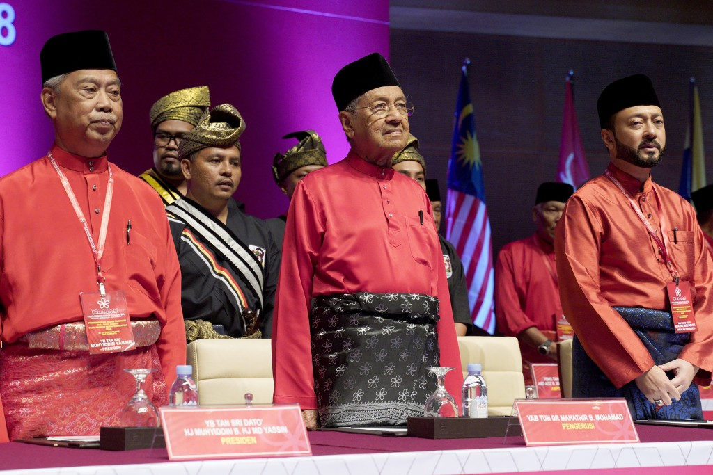 FILE- In this Dec. 29, 2018, file photo, Malaysian Prime Minster Mahathir Mohamad, center, stands next to his son Malaysian United Indigenous Party Vi...