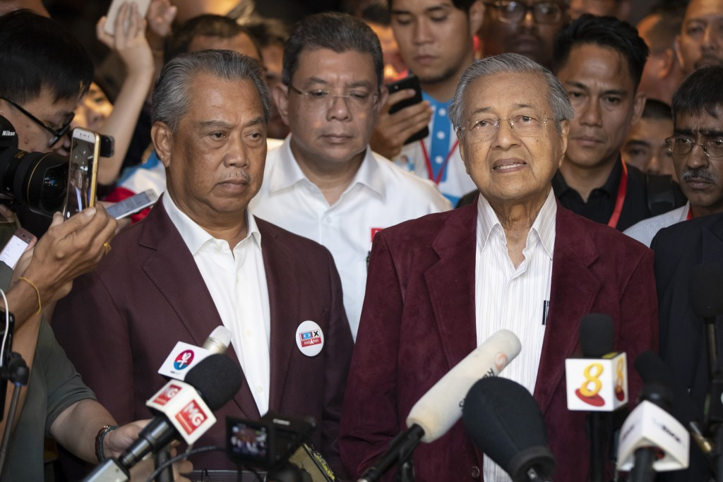 In this May 9, 2018, photo, Mahathir Mohamad, right, speaks to media during a press conference to announce victory on election as Muhyiddin Yassin, pr...