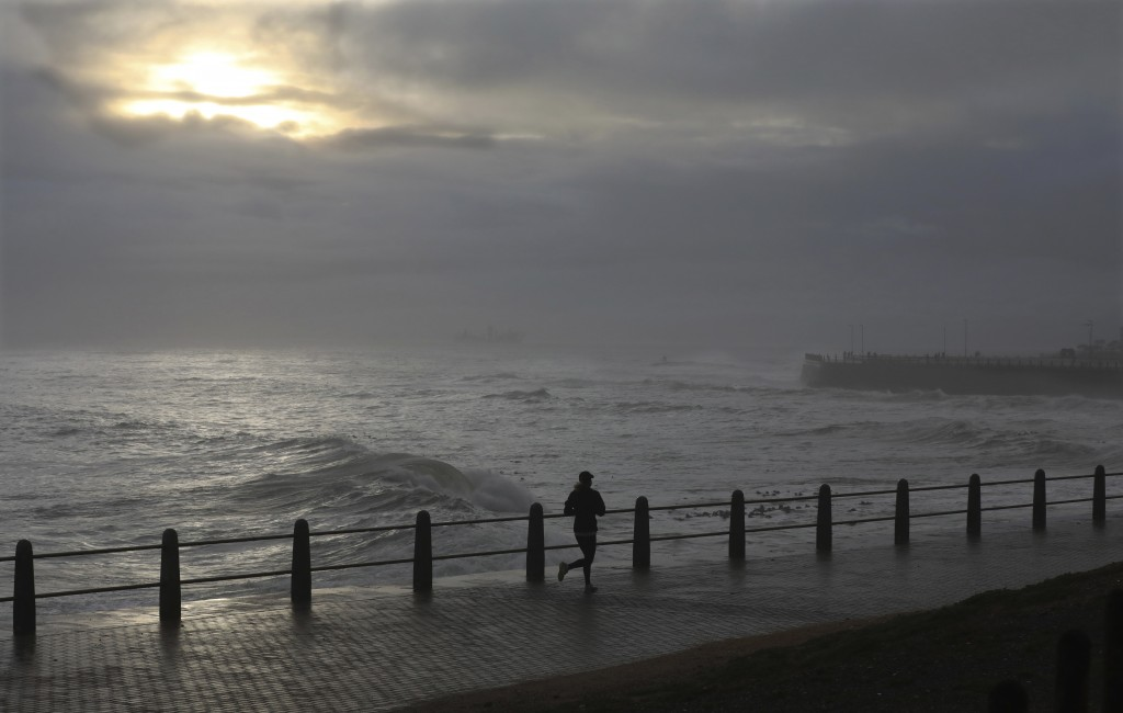 A woman runs on the promenade in stormy weather in Sea Point, Cape Town, South Africa, Friday, May 29, 2020. With dramatically increased community tra...