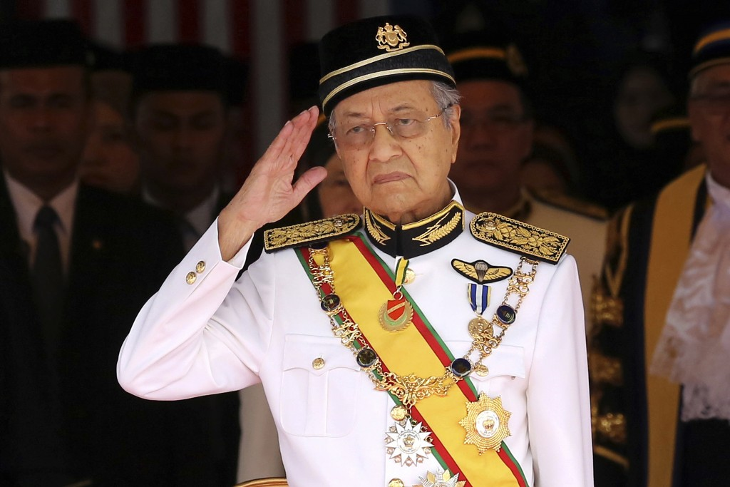 FILE - In this July 17, 2018, file photo, Malaysian Prime Minister Mahathir Mohamad salutes during the opening of the 14th parliament session at the P...