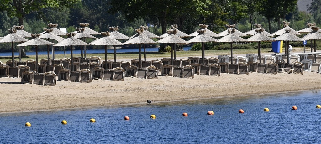 Parasols wait for tourists on a hot summer day at a lake in Xanten, Germany, Thursday, May 28, 2020. Germany's states, which determine their own coron...