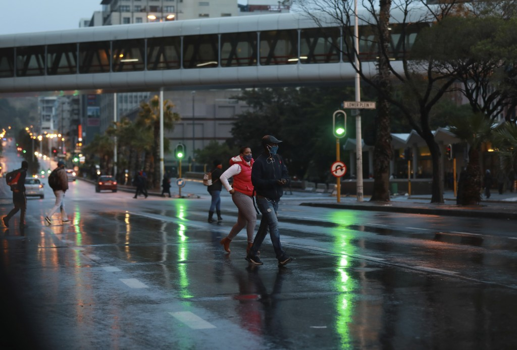 People cross a road in a stormy Cape Town, South Africa, Friday, May 29, 2020. With dramatically increased community transmissions, Cape Town has beco...