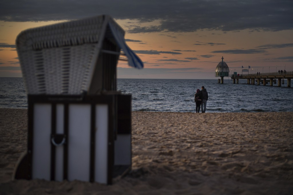 In this Monday May 25, 2020 photo, two tourists stand on the beach on the Baltic island of Usedom near the city of Zinnowitz, Germany. Germany's state...