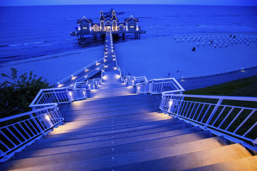 In this Friday May 22, 2020 photo, a restaurant a illuminated on a pier in Sellin on the island Ruegen, Germany. Germany's states, which determine the...