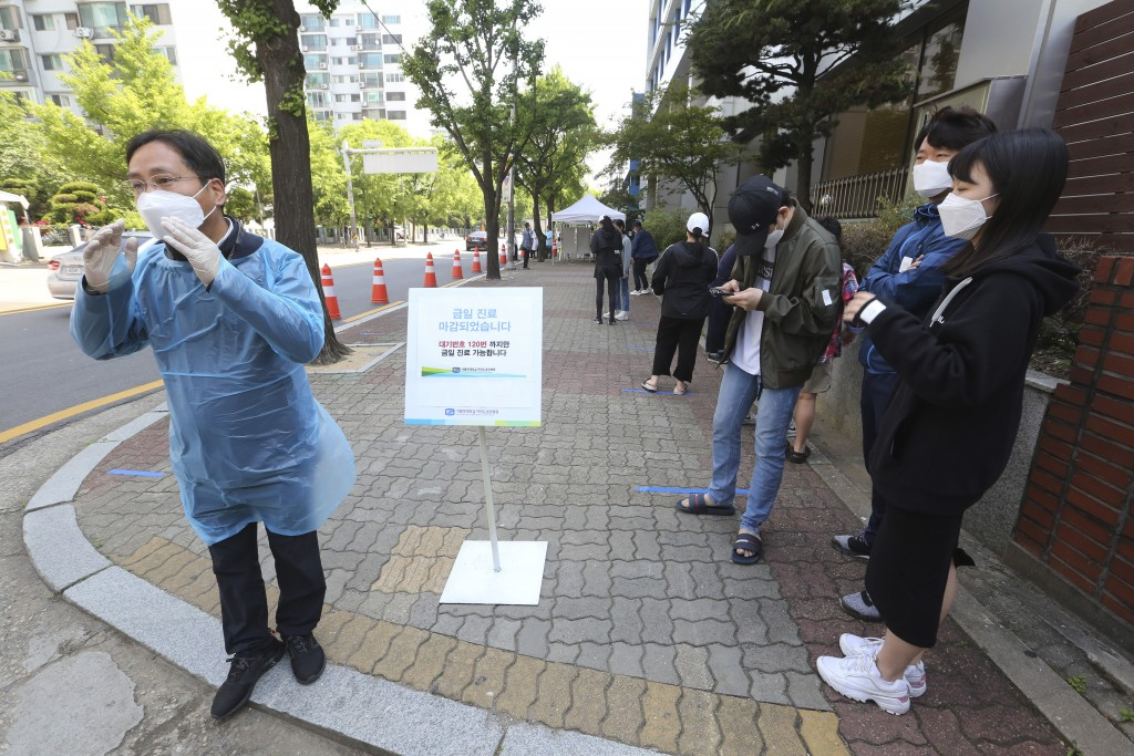 A medical staff, left, wearing a face mask shouts that the COVID-19 testing is over as people waiting for the test at a hospital in Seoul, South Korea...