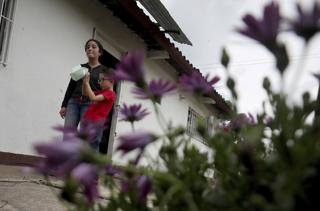 Marlene Beltran, 14, left, and her brother Felipe Beltran, 5, speak during an interview outside their home in Funza, Colombia, Wednesday, May 13, 2020...