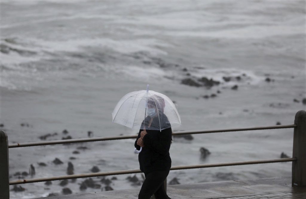 A woman walks on the promenade in stormy weather in Sea Point, Cape Town, South Africa, Friday, May 29, 2020. With dramatically increased community tr...