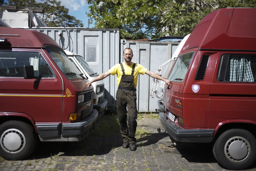 In this Tuesday, May 26, 2020 photo, Felix Rascher poses for a photo between Volkswagen camper vans he rent to tourists in a yard in Berlin, Germany. ...