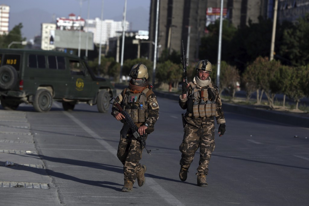 Afghan security forces inspect the site where a bus carrying local TV station employees hit a roadside bomb in Kabul, Afghanistan, Saturday, May 30, 2...