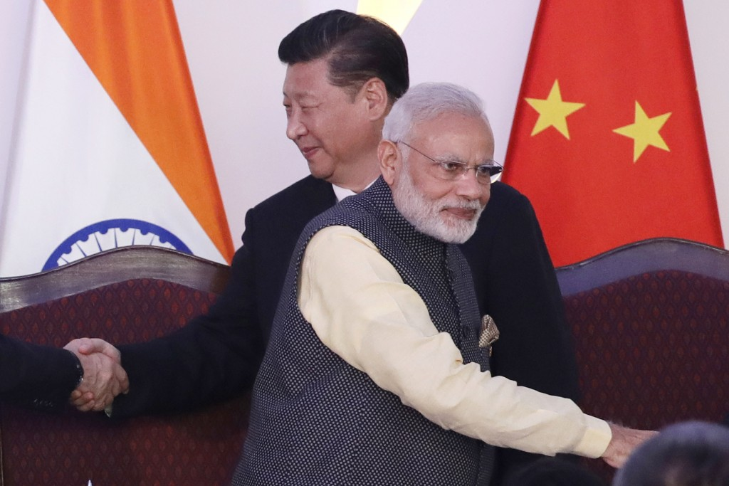 In this Oct. 16, 2016, file photo, Indian Prime Minister Narendra Modi, front and Chinese President Xi Jinping shake hands with leaders at the BRICS s...