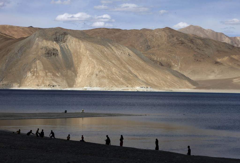 In this July 22, 2011 file photo, people stand by the banks of the Pangong Lake, near the India-China border in Ladakh, India.Indian officials say Ind...