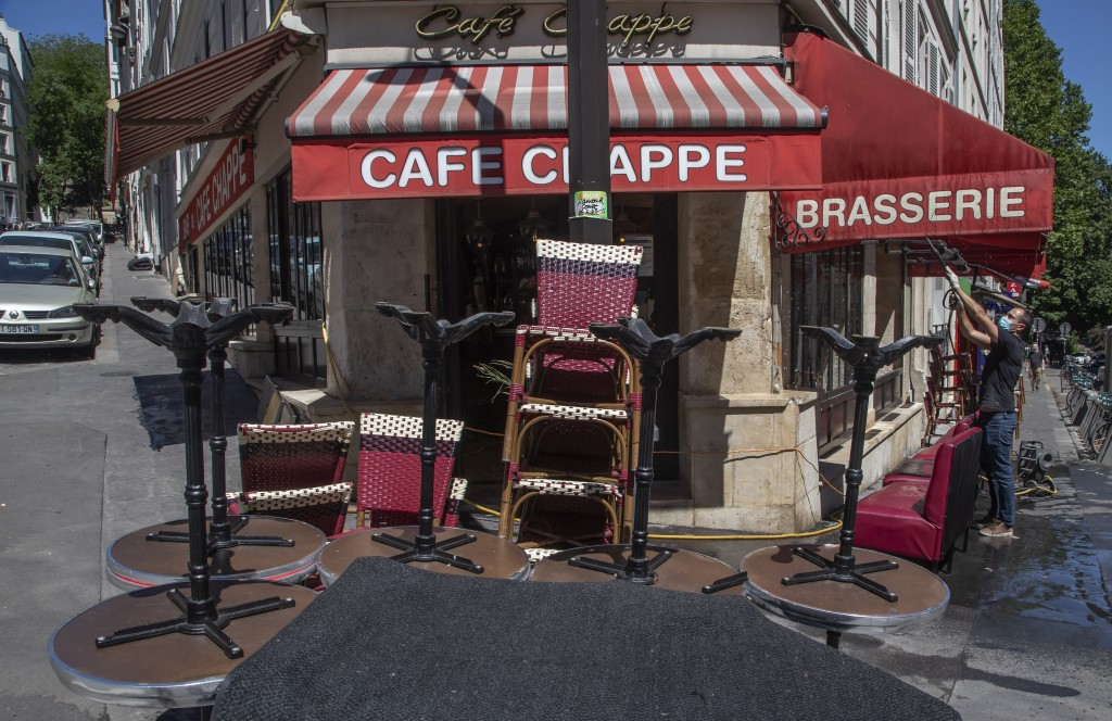 A man wears a mask to help curb the spread of the coronavirus cleans the terrace of his restaurant in Paris, Friday, May 29, 2020, as France gradually...