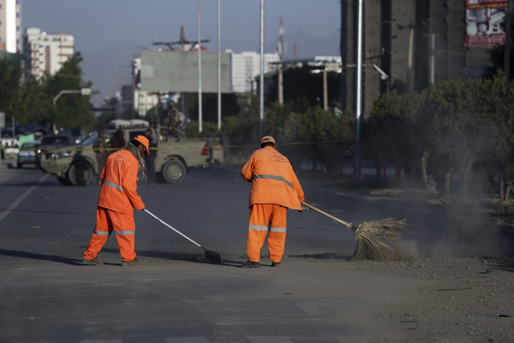 Afghan Municipality workers sweep a road after bomb explosion that targeted a bus carrying local TV station employees in Kabul, Afghanistan, Saturday,...