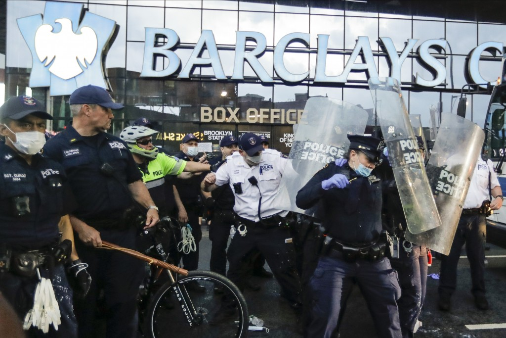 Police officers protect themselves with shields as protesters throw debris during a rally Friday, May 29, 2020, in the Brooklyn borough of New York, a...