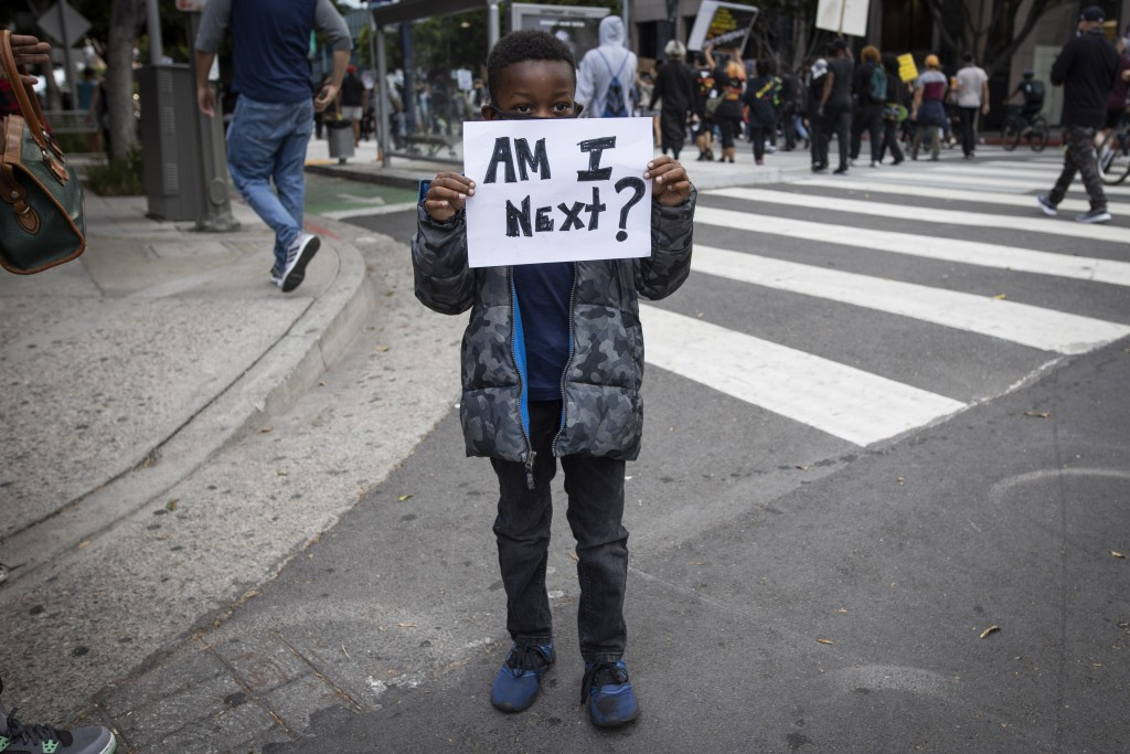 A boy holds a sign during a protest in downtown Los Angeles, Friday, May 29, 2020, over the death of George Floyd, who died in police custody on Memor...