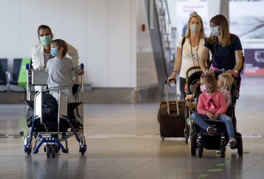 Wives and children of German business men working in China walk through a terminal at the airport in Frankfurt, Germany, Friday, May 29, 2020. Togethe...