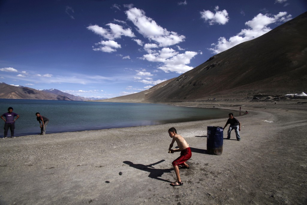 In this July 22, 2011, file photo, children play cricket by Pangong Lake, near the India-China border in Ladakh, India. Indian officials say Indian an...