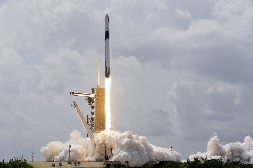 A SpaceX Falcon 9, with NASA astronauts Doug Hurley and Bob Behnken in the Crew Dragon capsule, lifts off from Pad 39-A at the Kennedy Space Center in...