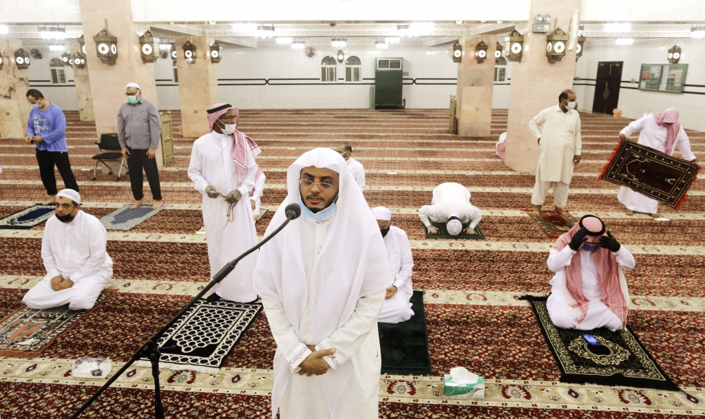 Saudi cleric Hammoud Al-Labban recites the call to prayers as worshippers wearing face masks and observing social distancing guidelines to protect aga...