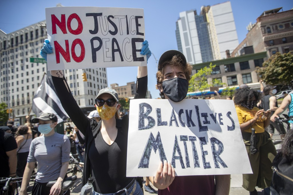 Demonstrators participate in a solidarity rally for George Floyd, Saturday, May 30, 2020, in the Harlem neighborhood of New York. Floyd died after Min...