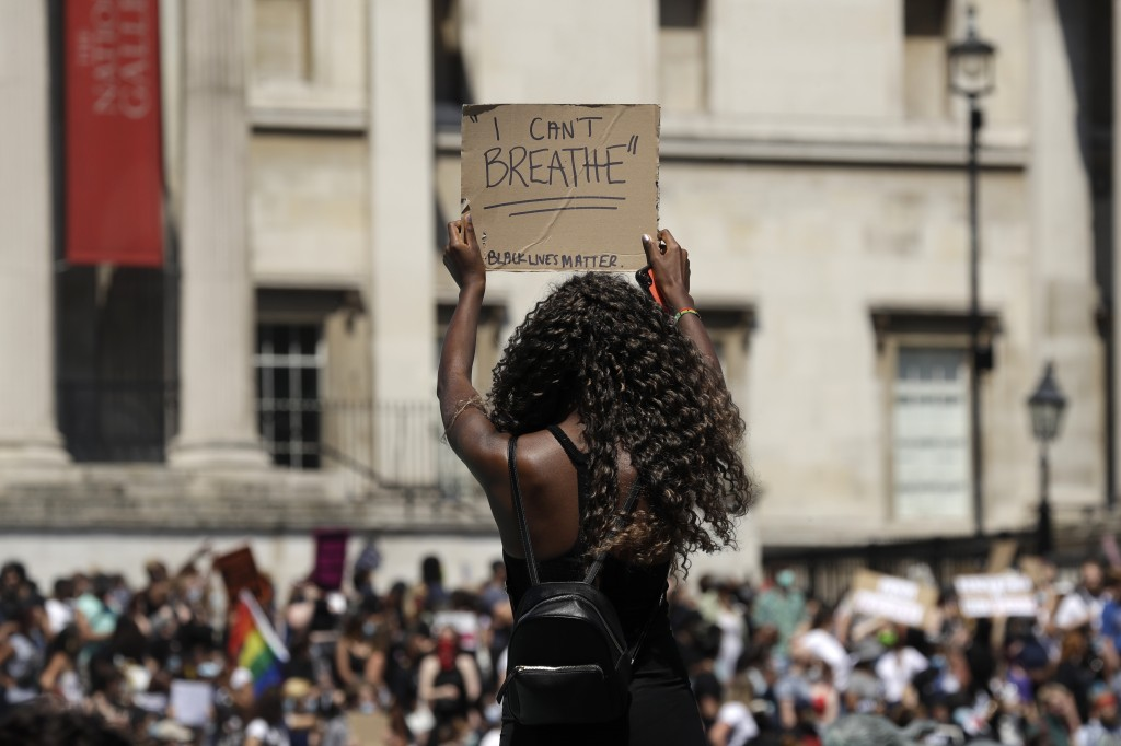 A woman holds up a banner as people gather in Trafalgar Square in central London on Sunday, May 31, 2020 to protest against the recent killing of Geor...