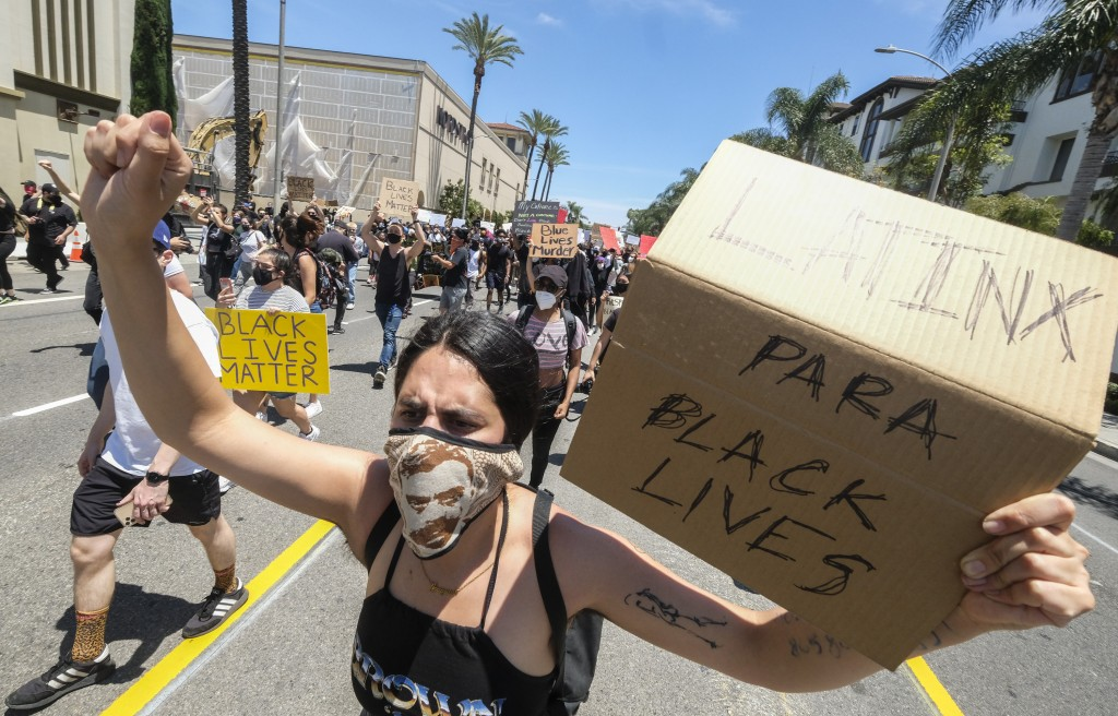 A woman holds a sign during a protest over the death of George Floyd in Los Angeles, Saturday, May 30, 2020. Protests across the country have escalate...