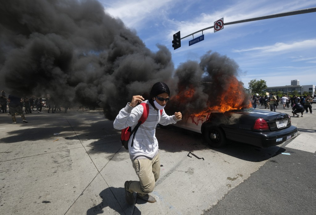 A protester runs while a police vehicle is burning during a protest over the death of George Floyd in Los Angeles, Saturday, May 30, 2020.Protests acr...