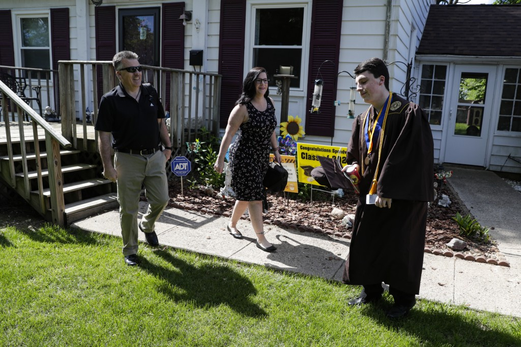 Jacob Foxworthy, right, and his parents Ted and Cindy Foxworthy leave their home to attend the Speedway High School graduation ceremony at the Indiana...