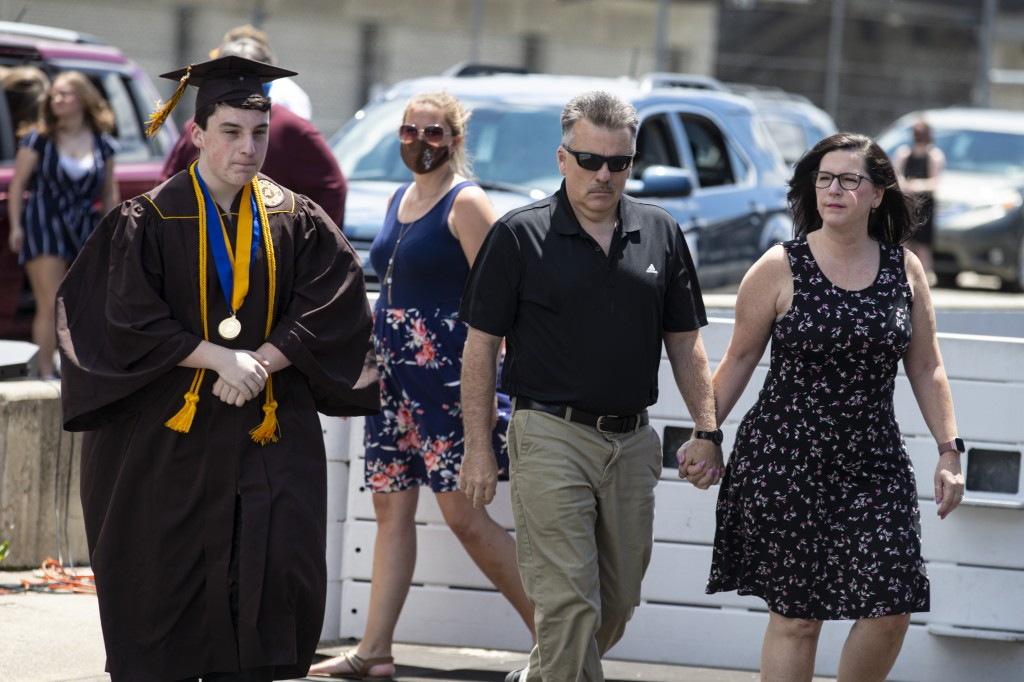 Jacob Foxworthy, left, walks onto the track with his parents Ted and Cindy Foxworthy to receive his Speedway High School diploma during a ceremony at ...