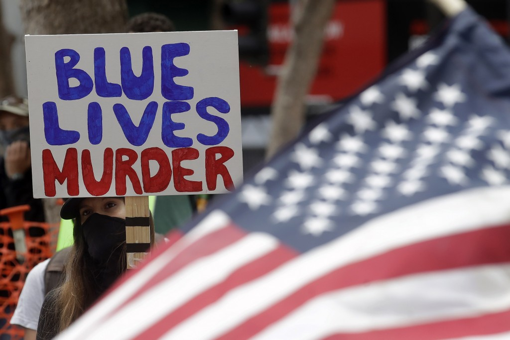 A woman holds a sign at a protest over the Memorial Day death of George Floyd, a handcuffed black man in police custody in Minneapolis, in San Francis...