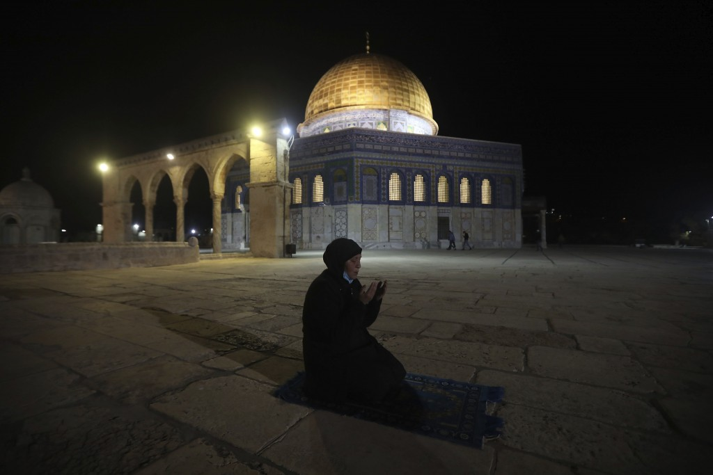 A muslim woman pray next to the Dome of the Rock Mosque in the Al Aqsa Mosque compound in Jerusalem's old city, Sunday, May 31, 2020.The Al-Aqsa mosqu...