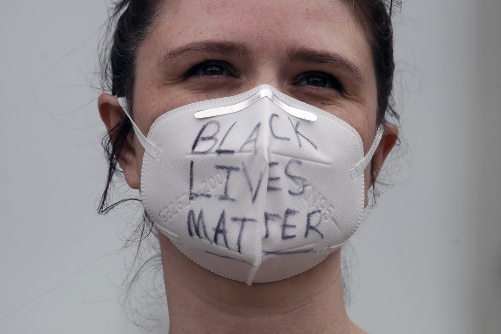 Annah Dominis wears a face mask  with Black Lives Matter written on it, in San Francisco, Saturday, May 30, 2020,.at a protest over the Memorial Day d...