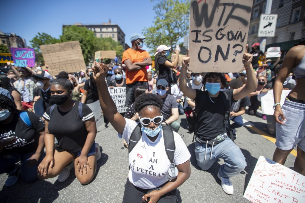 Protesters take a knee while marching through Harlem during a solidarity rally for George Floyd, Saturday, May 30, 2020, in New York. Floyd died after...