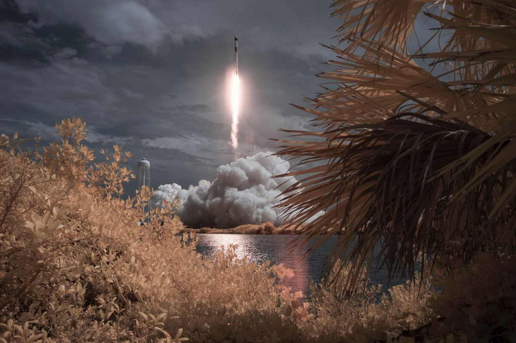 In this photo provided by NASA, a SpaceX Falcon 9 rocket carrying the company's Crew Dragon spacecraft is seen in this false color infrared exposure a...