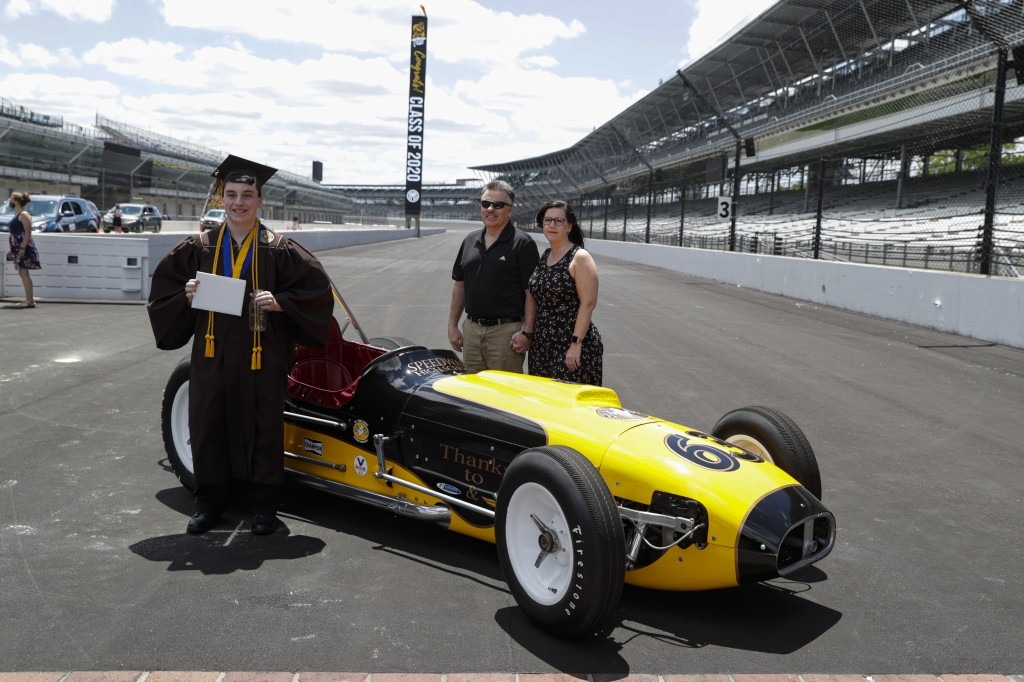 Jacob Foxworthy, left, poses with his parents Ted and Cindy Foxworthy around a vintage race car after he received his Speedway High School diploma dur...