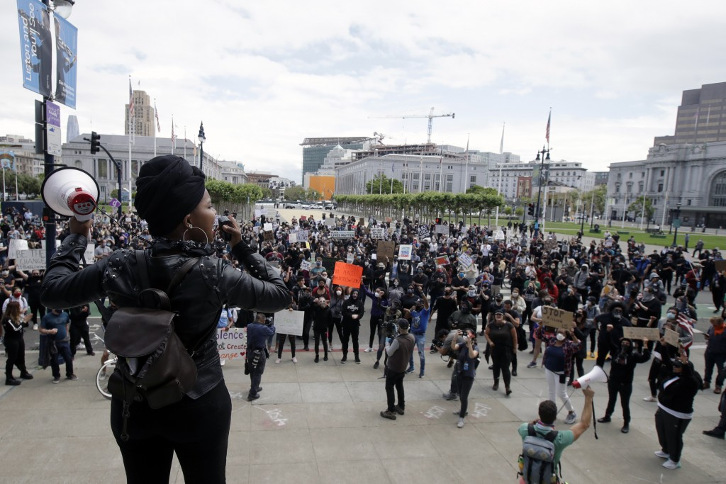 Raiah Sinn, foreground, speaks at a protest over the Memorial Day death of George Floyd, a handcuffed black man in police custody in Minneapolis, in S...
