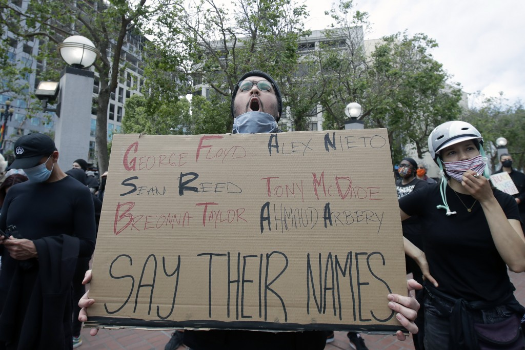 Nolan Ramirez holds up a sign at protest over the Memorial Day death of George Floyd, a handcuffed black man in police custody in Minneapolis, in San ...