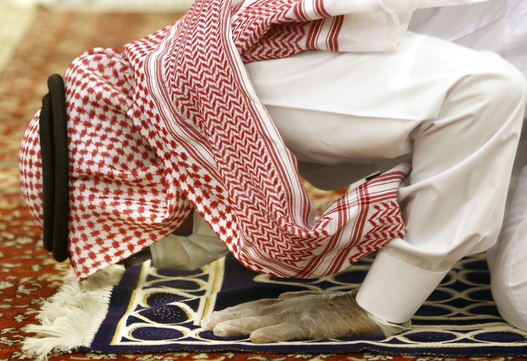 A Saudi worshipper wearing a face mask and gloves to prevent the spread of COVID-19 as he prays dawn prayers at al-Mirabi Mosque in Jiddah, Saudi Arab...