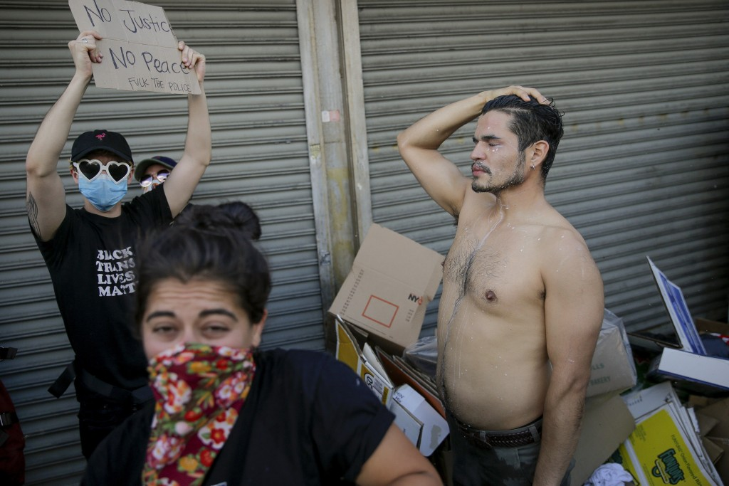 Protesters react after being hit with pepper spray from police officers during a demonstration Saturday, May 30, 2020, in the Brooklyn borough of New ...