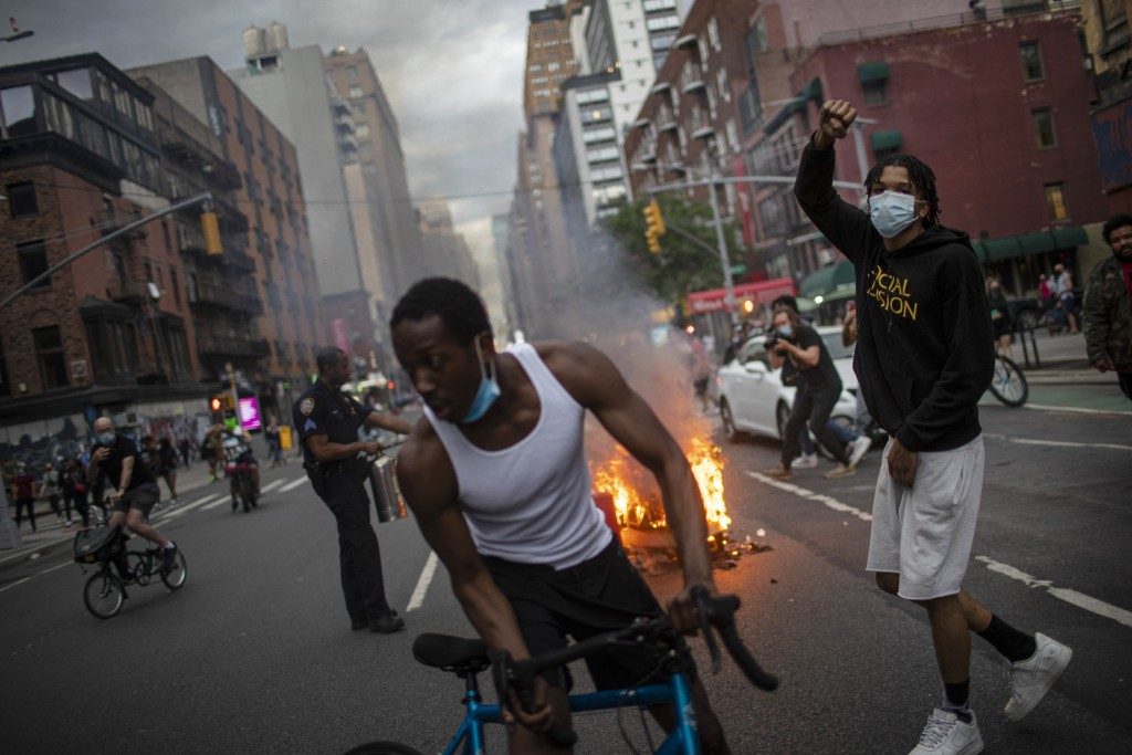 Protesters march down the street as trash burns in the background during a solidarity rally for George Floyd, Saturday, May 30, 2020, in New York. Pro...