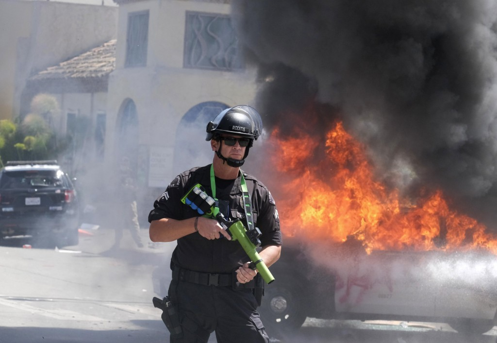 A police officer stands guard while a police vehicle burns during a protest over the death of George Floyd in Los Angeles, Saturday, May 30, 2020. Pro...