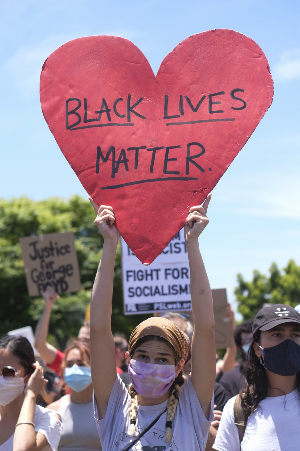 A protester holds a sign during a protest in Los Angeles, Saturday, May 30, 2020. Demonstrators took to the streets of Los Angeles to protest the deat...