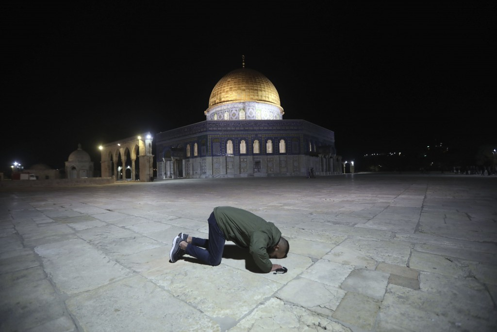 A muslim man pray next to the Dome of the Rock Mosque in the Al Aqsa Mosque compound in Jerusalem's old city, Sunday, May 31, 2020.The Al-Aqsa mosque ...