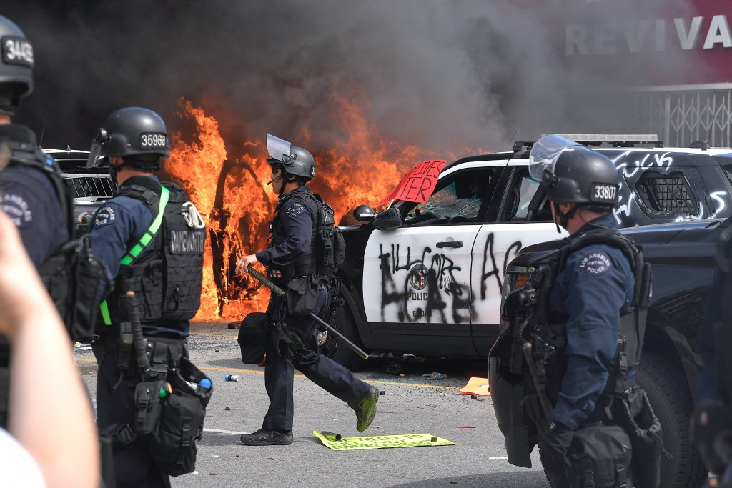 A police car burns as another one is seen destroyed during a protest over the death of George Floyd Saturday, May 30, 2020, in Los Angeles. Floyd died...