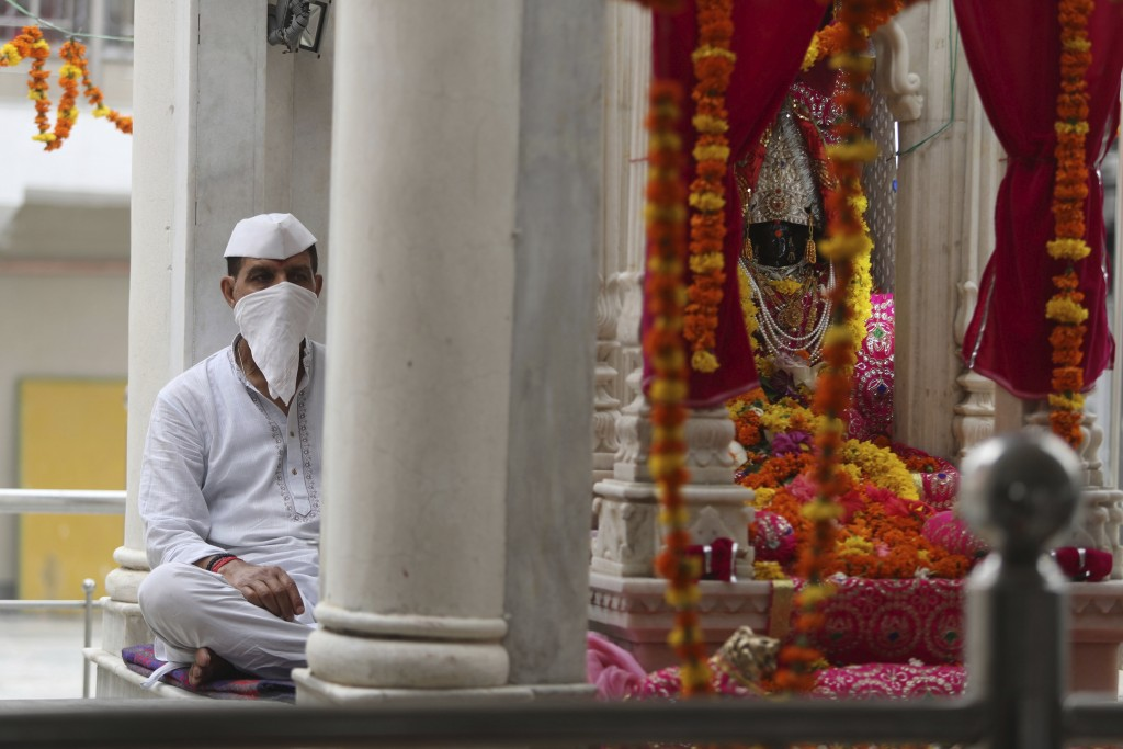 A priest wearing a mask sits to perform rituals during the annual festival at Kheer Bhawani temple amid the Coronavirus pandemic in Jammu, India, Satu...