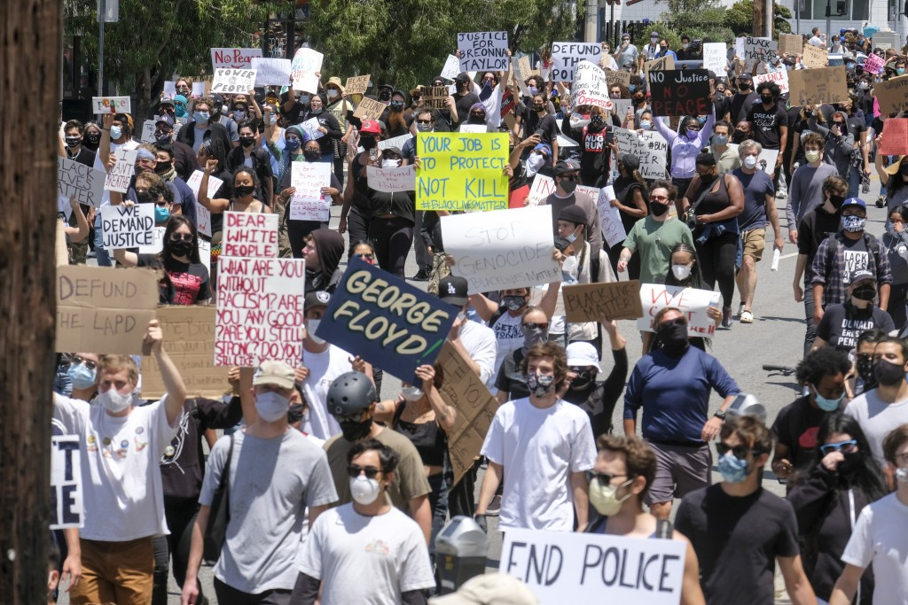 Protesters march on a street during a protest over the death of George Floyd, who died on Memorial Day after being taken into custody by Minneapolis p...